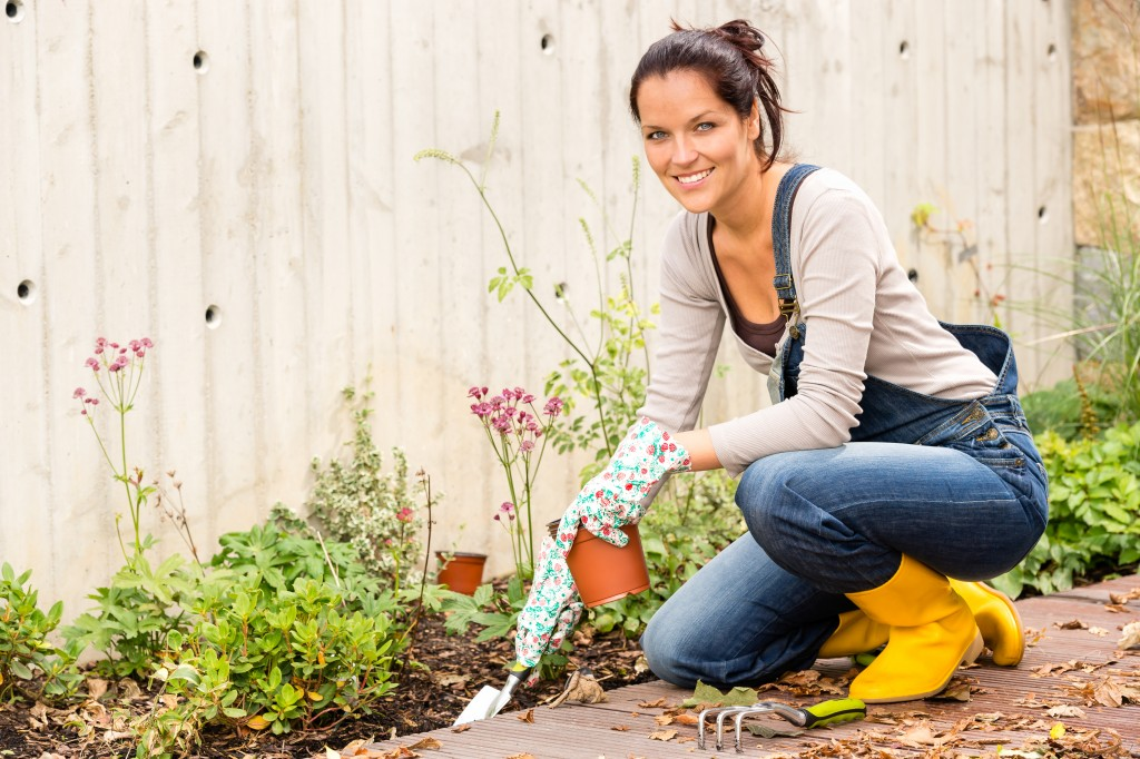 Woman posing while holding a small shovel for her garden