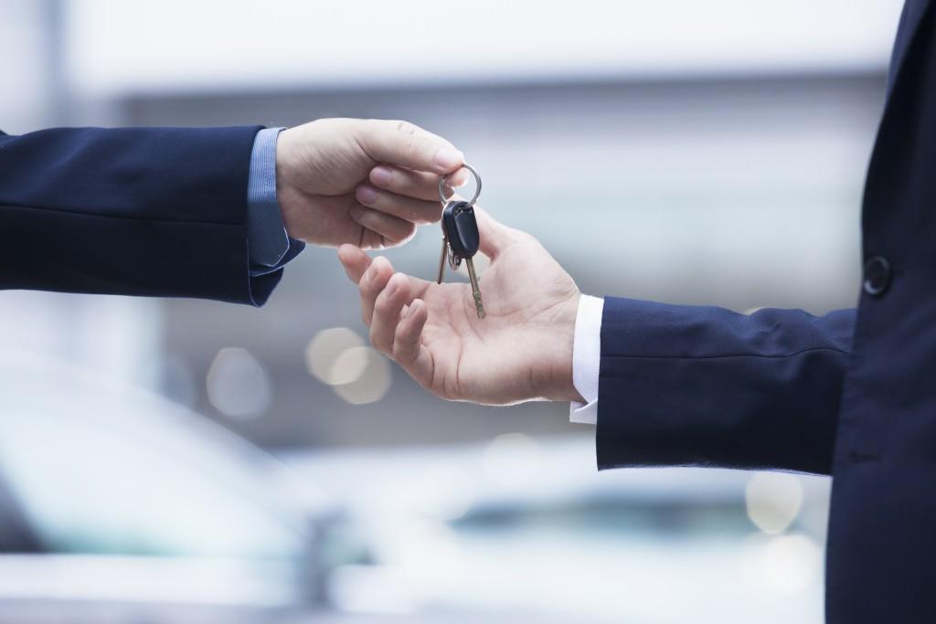 Car salesman handing over car keys