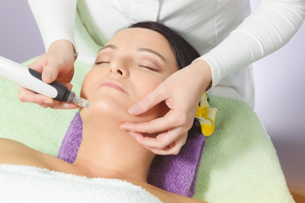 Woman having mesotherapy facial treatment at beauty salon