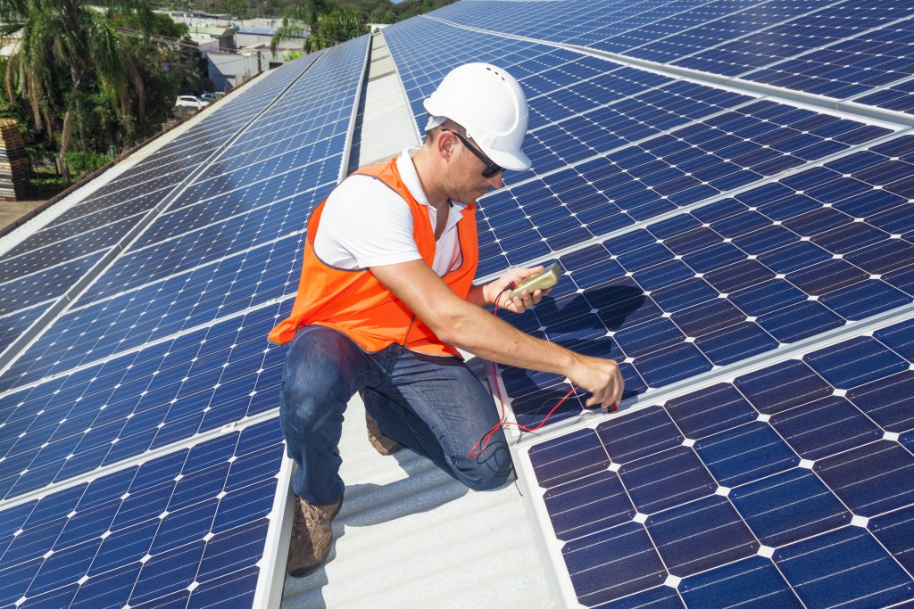 Young technician checking solar panels on factory roof