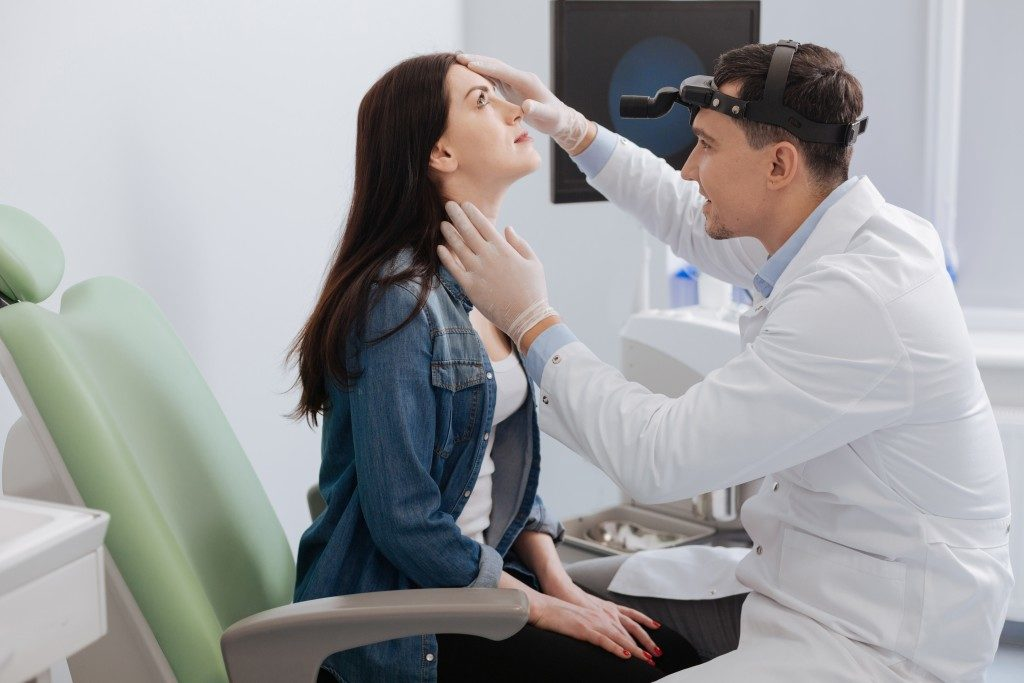 doctor checking the throat of a woman