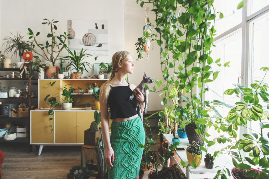 woman with kat inside her house with indoor plants