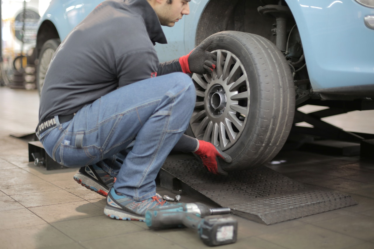 person replacing car tire