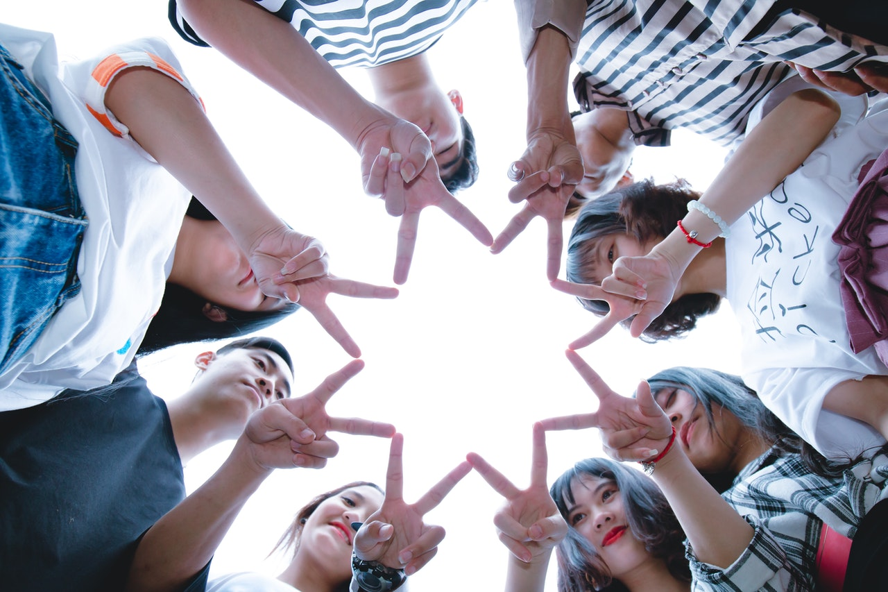 group of young people forming star with their fingers