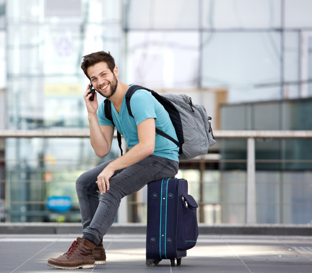 sitting on suitcase and calling by cellphone at airport