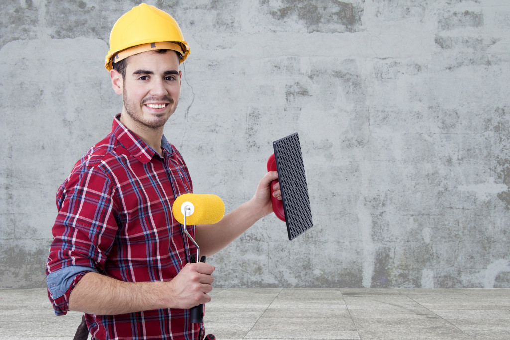 Man holding a paint roller and a trowel